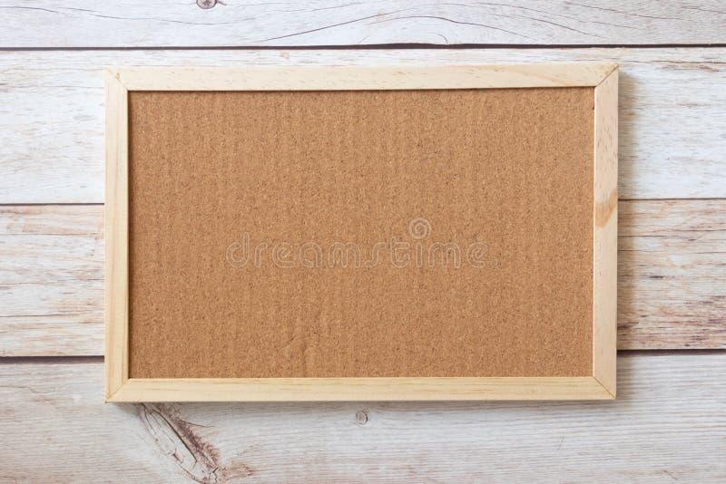 La vue plate de la moquerie vide de panneau de liège décorent des autocollants sur la table en bois Secteur simple pour l'espace  photo libre de droits