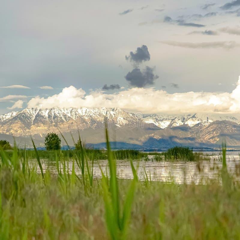La vue scénique de nature de place avec un lac et une neige brillants a couvert la montagne sous le ciel nuageux photographie stock