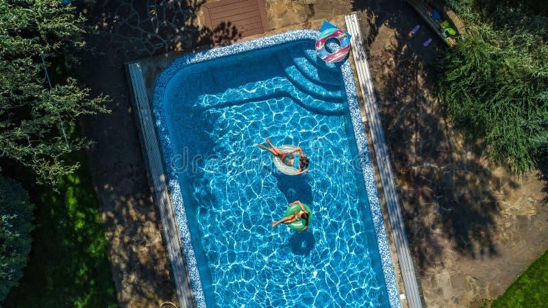 La vue supérieure aérienne des enfants dans la piscine d'en haut, les enfants heureux nagent sur les butées toriques gonflables d photos stock