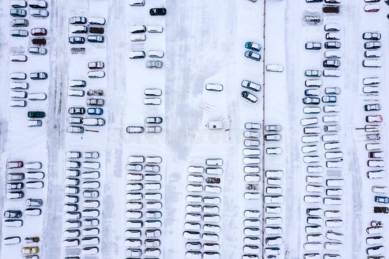 La vue supérieure aérienne des voitures couvertes de neige se tiennent dans le parking image libre de droits