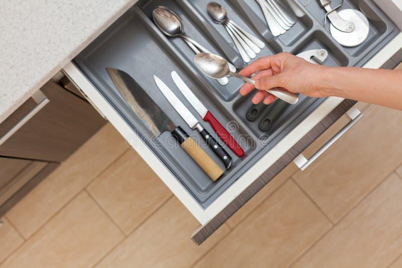 La vue supérieure courbe a cultivé la photo du tiroir ouvert de cuisine de main de femme par la poignée de porte moderne, avec le photos stock