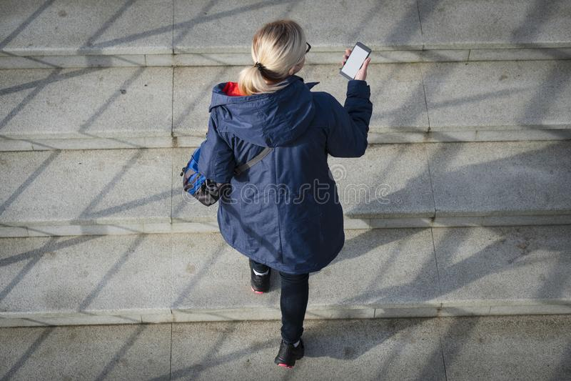 La vue supérieure d'une femme utilise le téléphone intelligent tandis que se tient sur le Ba images stock