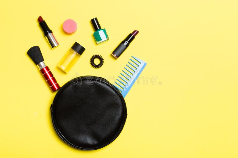 La vue supérieure de composent des produits tombés hors des cosmétiques mettent en sac sur le fond jaune Concept cosmétique avec  photographie stock libre de droits
