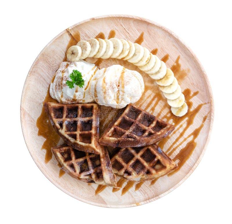 La vue supérieure de la crème glacée de gaufre et avec la banane coupée en tranches en bois plat d'isolement sur le fond blanc, c photographie stock