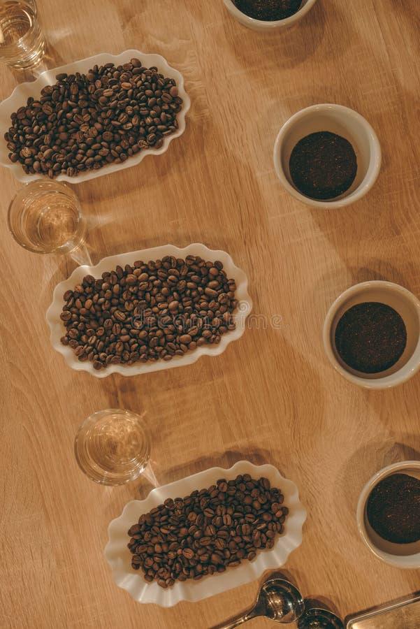 la vue supérieure de la disposition des cuvettes avec des grains de café et les verres de l'eau pour la nourriture fonctionnent photos stock