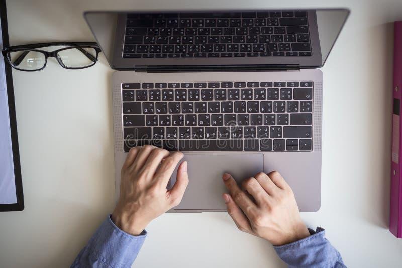 La vue supérieure de l'homme d'affaires remet occupé utilisant l'ordinateur portable images libres de droits