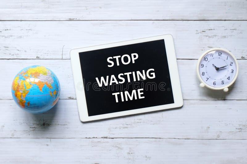 La vue supérieure de l'horloge de table, le globe et le comprimé écrits avec le message cessent de perdre le temps sur le fond en photographie stock libre de droits