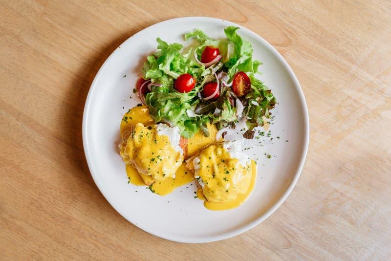 La vue supérieure de l'oeuf Benedict a servi avec de la salade dans le plat blanc sur la table en bois pour le petit déjeuner et  images libres de droits