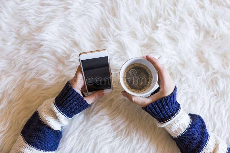 La vue supérieure de la femme remet tenir un téléphone intelligent au-dessus du fond blanc Tasse de café en outre lifestyles indo photographie stock