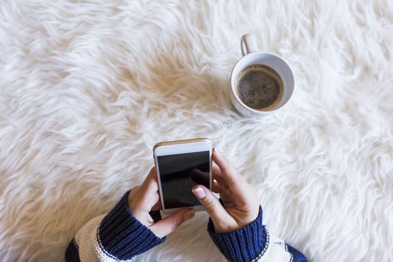 La vue supérieure de la femme remet tenir un téléphone intelligent au-dessus du fond blanc Tasse de café en outre lifestyles indo images libres de droits