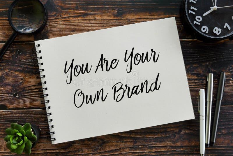 La vue supérieure de la loupe, l'usine, l'horloge, le stylo et le carnet écrits avec vous sont votre propre marque images libres de droits