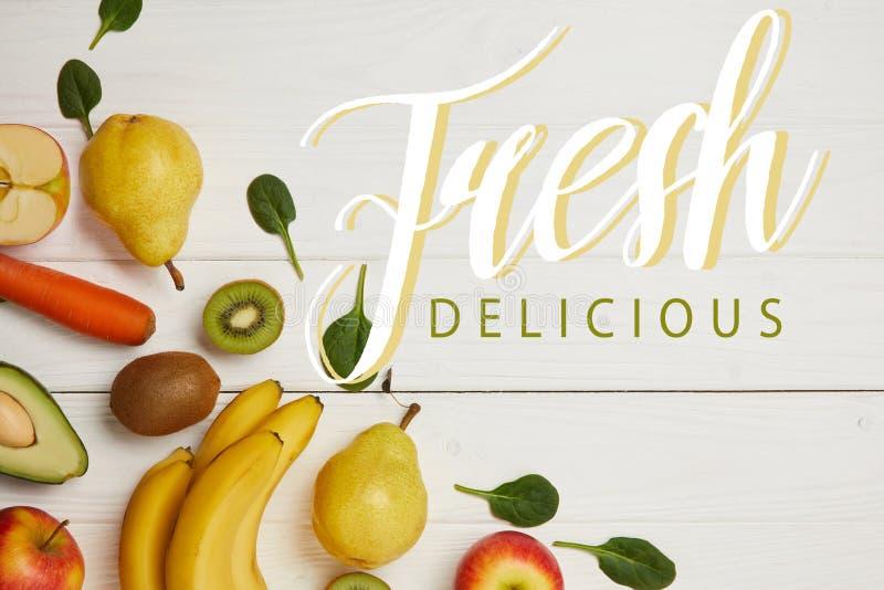 la vue supérieure des fruits frais et des épinards part sur le fond en bois blanc avec l'espace de copie, inscription délicieuse  photographie stock libre de droits