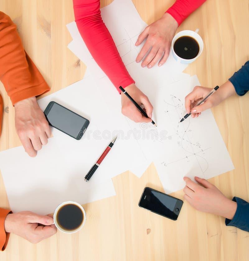 La vue supérieure des hommes d'affaires remet des stylos de participation, smartphone de papiers photos libres de droits