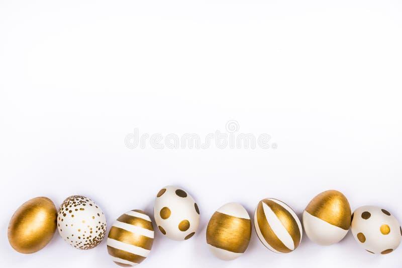 La vue supérieure des oeufs de pâques colorés avec la peinture d'or differen dedans des modèles Diverses conceptions rayées et po photo libre de droits