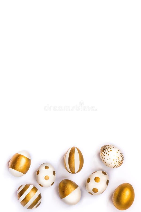 La vue supérieure des oeufs de pâques colorés avec la peinture d'or differen dedans des modèles Diverses conceptions rayées et po image stock
