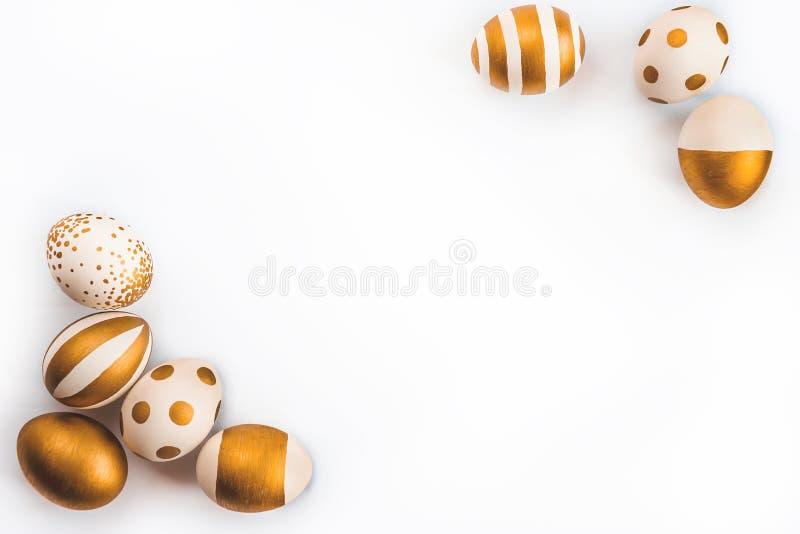 La vue supérieure des oeufs de pâques colorés avec la peinture d'or differen dedans des modèles Diverses conceptions rayées et po photographie stock