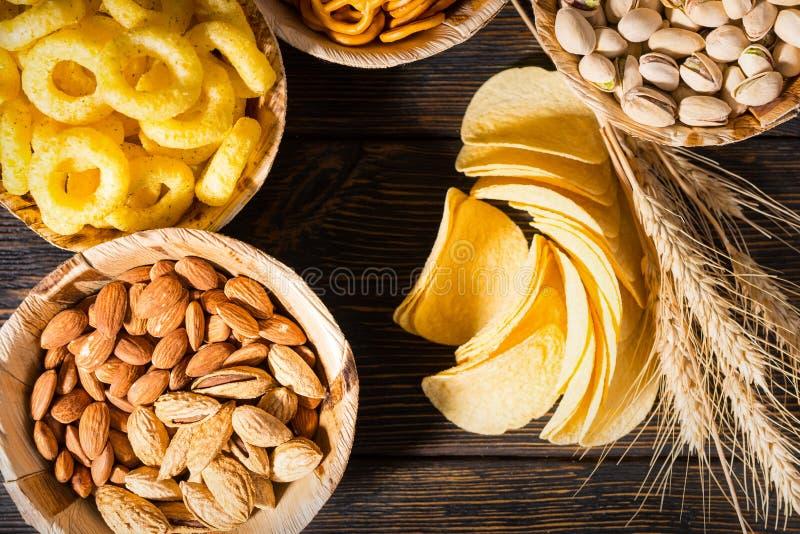 La vue supérieure des plats avec des pistaches, les écrous et d'autres casse-croûte s'approchent de W photographie stock libre de droits