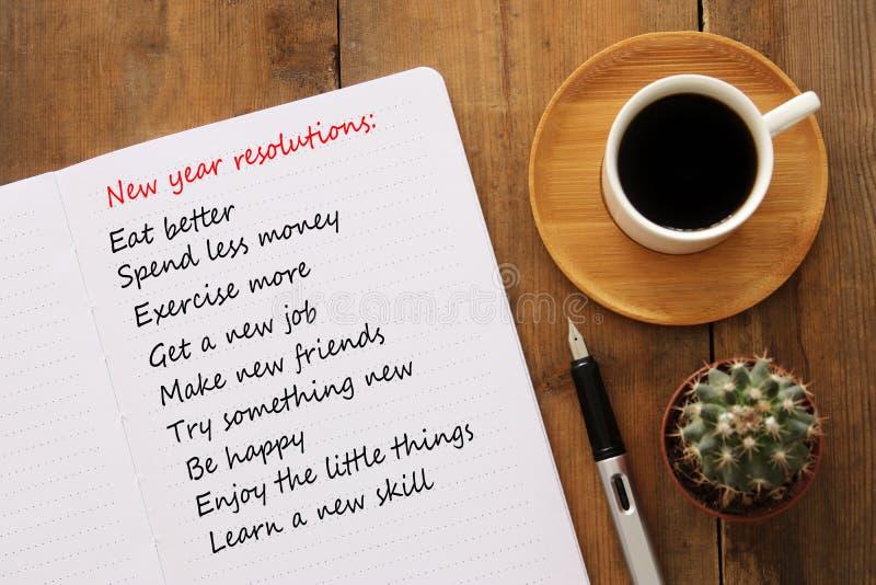 La vue supérieure des résolutions de nouvelle année énumèrent avec le carnet, tasse de café au-dessus de bureau en bois photo libre de droits