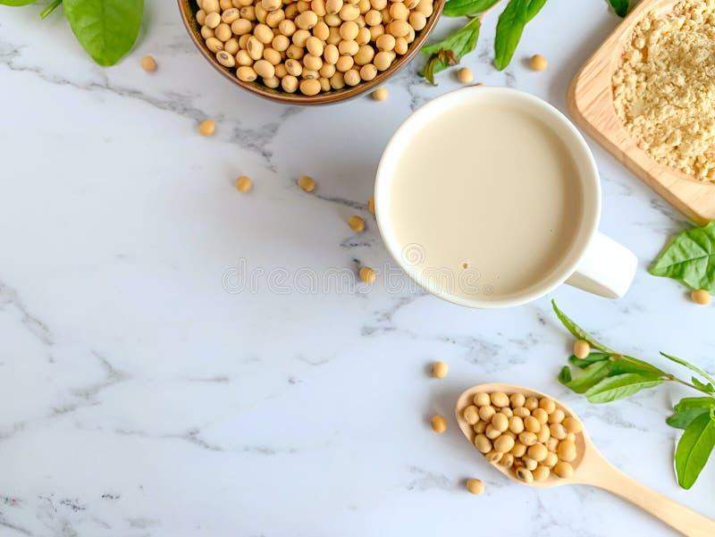 La vue supérieure des tasses de lait de soja, tasse de graines de soja, haricots de soja a placé sur une cuillère en bois photos stock