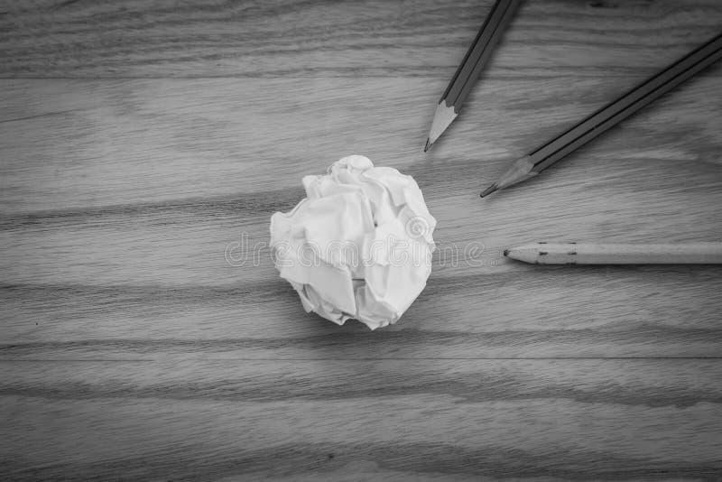 La vue supérieure du crayon trois avec le blanc a chiffonné la boule de papier mise sur le plancher en bois dans l'image noire et image libre de droits