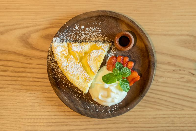 La vue supérieure du gâteau au fromage chaud de style japonais a servi avec la crème fouettée, la fraise fraîche et le sirop de m photos stock