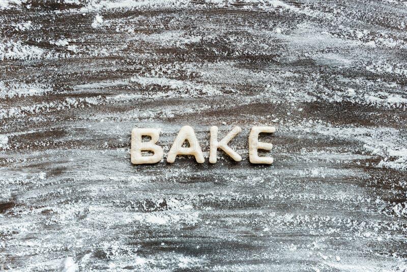 La vue supérieure du mot font cuire au four fait à partir de la pâte de biscuit avec de la farine images stock