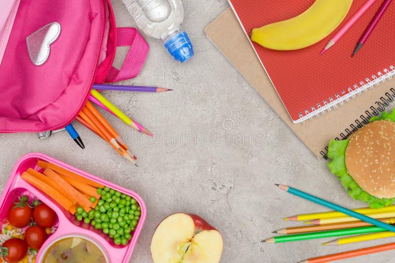 la vue supérieure du plateau avec des enfants déjeunent pour l'école, les carnets et les crayons images libres de droits