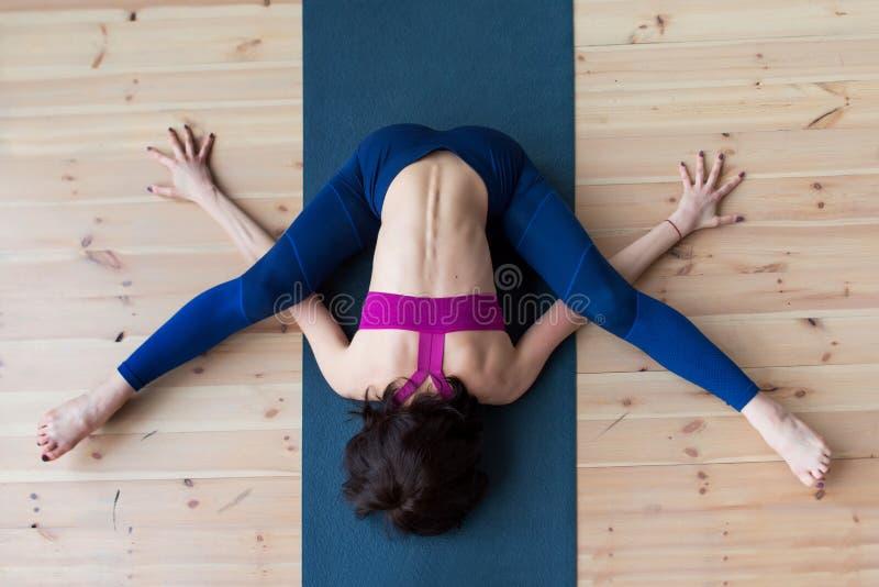 La vue supérieure du yogi féminin faisant la tortue avancée de kurmasana posent sur le tapis à l'intérieur tout en pratiquant le  photographie stock