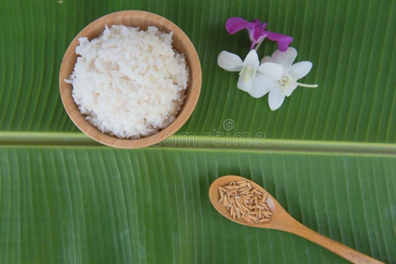 La vue supérieure a fait cuire le riz dans la cuvette sur la feuille verte de banane et le paddy dans la cuillère et l'orchidée photo libre de droits