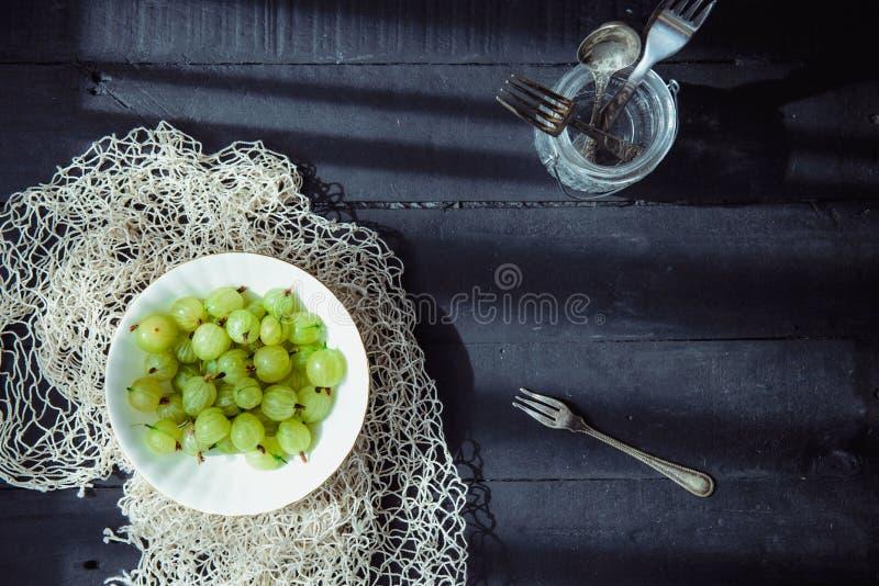 La vue supérieure a fraîchement sélectionné la groseille à maquereau fraîche verte mûre organique dans la cuvette en céramique su photographie stock libre de droits
