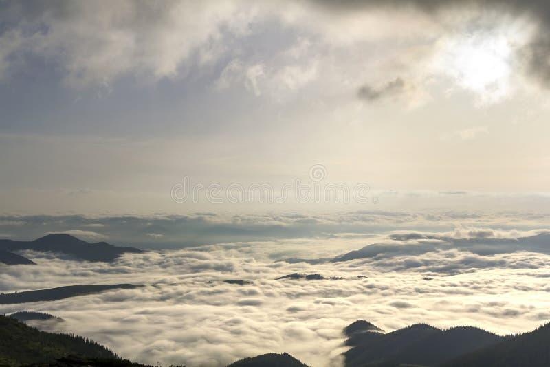 La vue supérieure large fantastique de la vallée de montagne a rempli de gonflé blanc comme les nuages et le brouillard de neige  images libres de droits