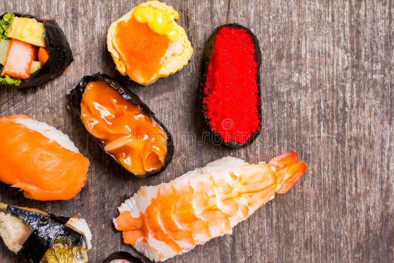 La vue supérieure, le sashimi de sushi et les petits pains de sushi réglés ont servi sur la table en bois photos stock