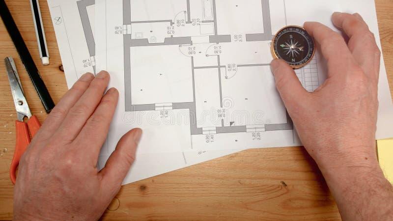 La vue supérieure, la main d'un architecte avec une boussole recherche l'orientation du Pôle Nord, longueur idéale pour des sujet image stock