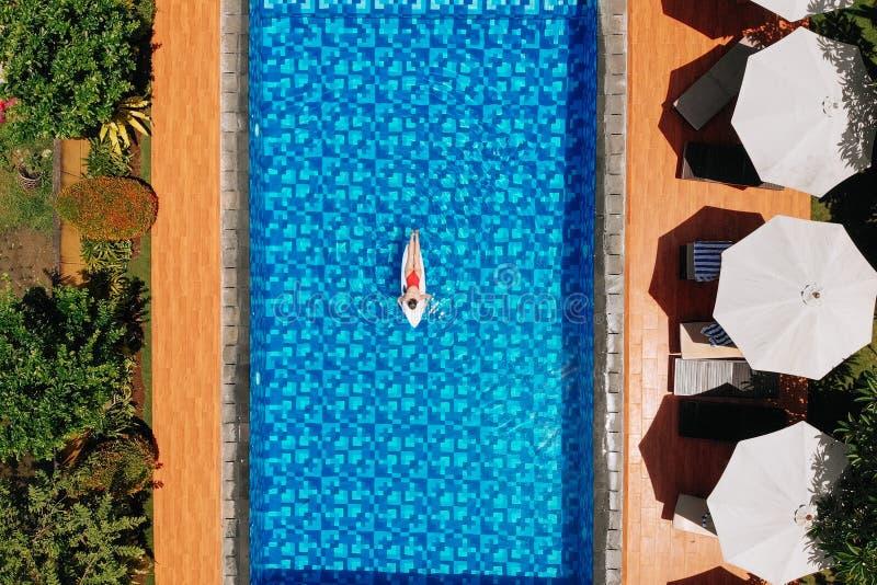 La vue sur la femme en bikini rouge se trouve sur la planche de surf de la piscine Voyage des filles et découverte du monde Voyag photo libre de droits