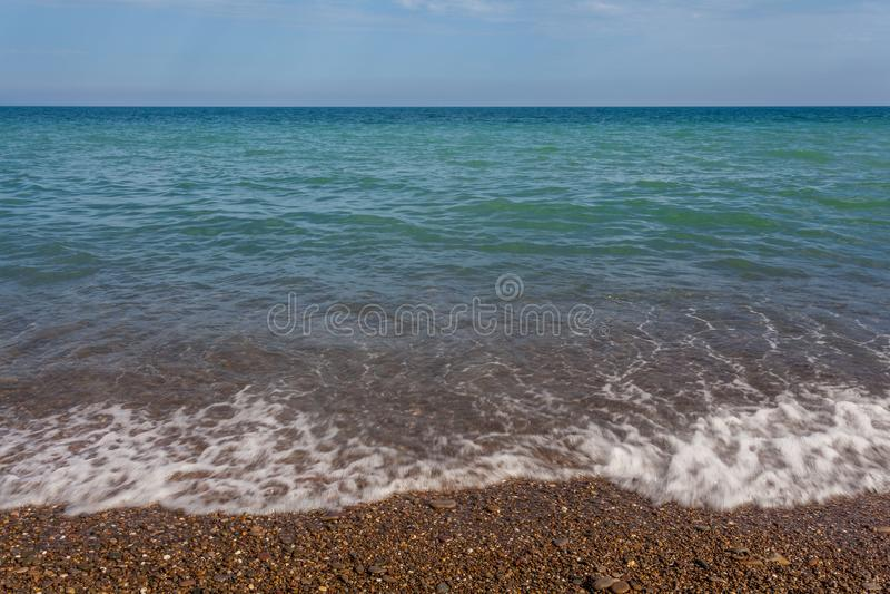 La vue vers le bas sur la vague de mer roule sur le rivage du bardeau photo libre de droits