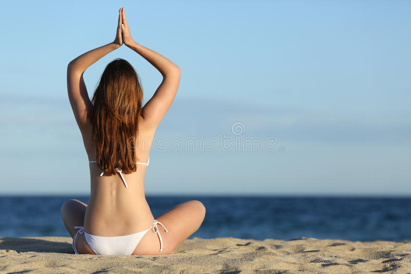 La yoga practicante de la mujer ejercita en la playa en verano imagenes de archivo