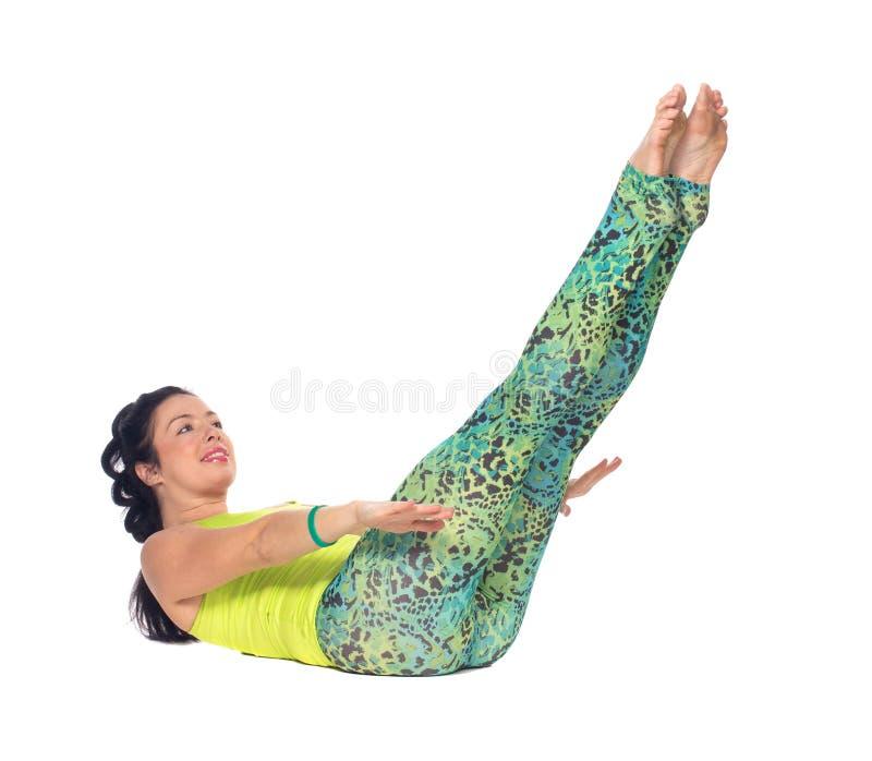 La yoga practicante de la mujer joven, mintiendo encendido apoya con los pies encima del variatio fotografía de archivo
