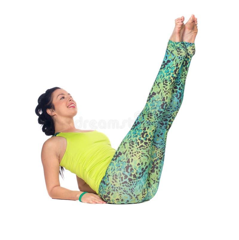 La yoga practicante de la mujer joven, mintiendo encendido apoya con los pies encima del variatio imagenes de archivo