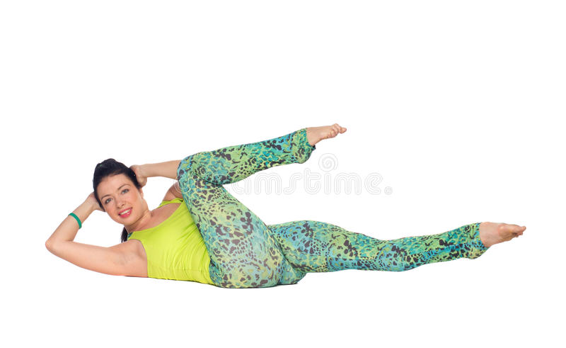 La yoga practicante de la mujer joven, mintiendo encendido apoya con los pies encima del variatio fotos de archivo
