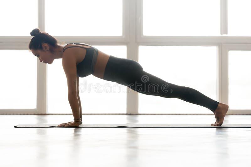 La yoga practicante de la mujer joven, haciendo pectorales o la prensa sube foto de archivo libre de regalías
