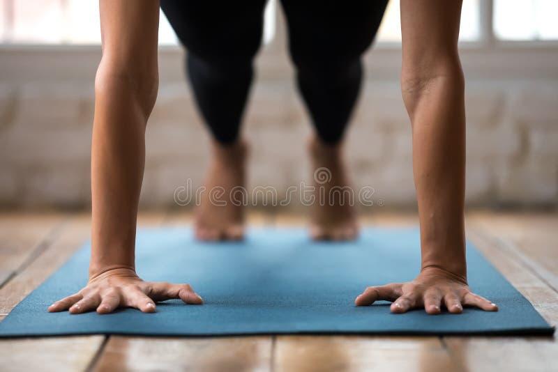 La yoga practicante de la mujer joven, haciendo pectorales o la prensa sube fotografía de archivo libre de regalías
