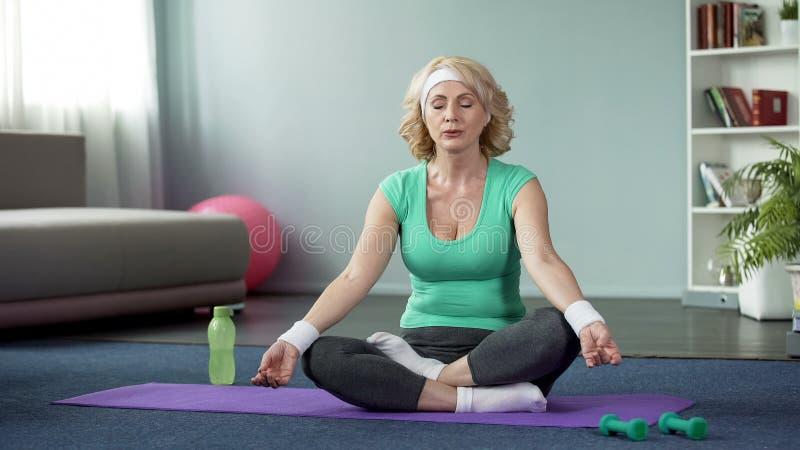 La yoga practicante de la señora madura en casa, haciendo la relajación ejercita, meditación imagenes de archivo