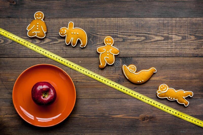 La yoga y la dieta sana para pierden el peso Placa, manzana, cinta métrica y galletas en la forma de los asans de la yoga en de m foto de archivo libre de regalías