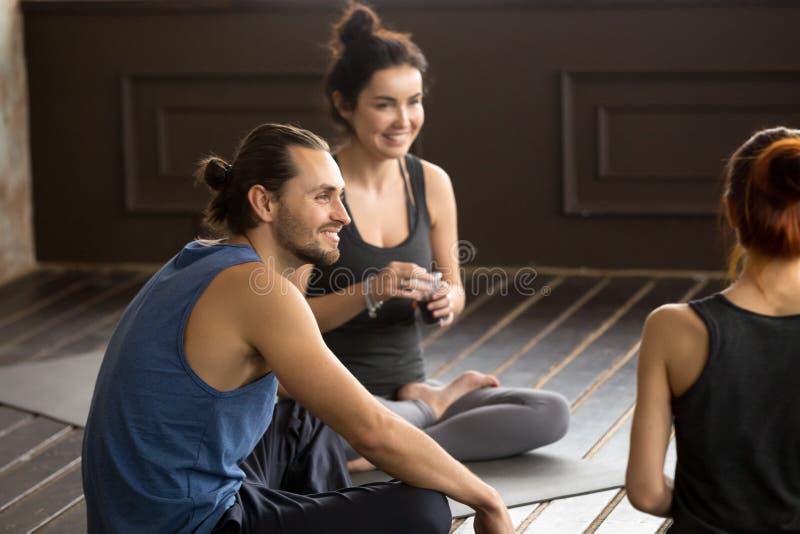 La yogui atenta sonriente sirve sentarse en la estera en el entrenamiento del grupo imágenes de archivo libres de regalías