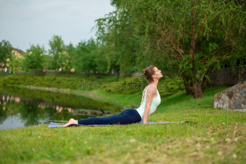 La yogui morena joven delgada no realiza ningún ejercicio complicado de la yoga en la hierba verde en verano contra la perspectiv fotografía de archivo