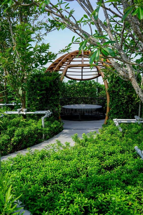 La zona de descanso en un jardín con la estructura moderna del metal y el sofá negro en piso concreto fotografía de archivo