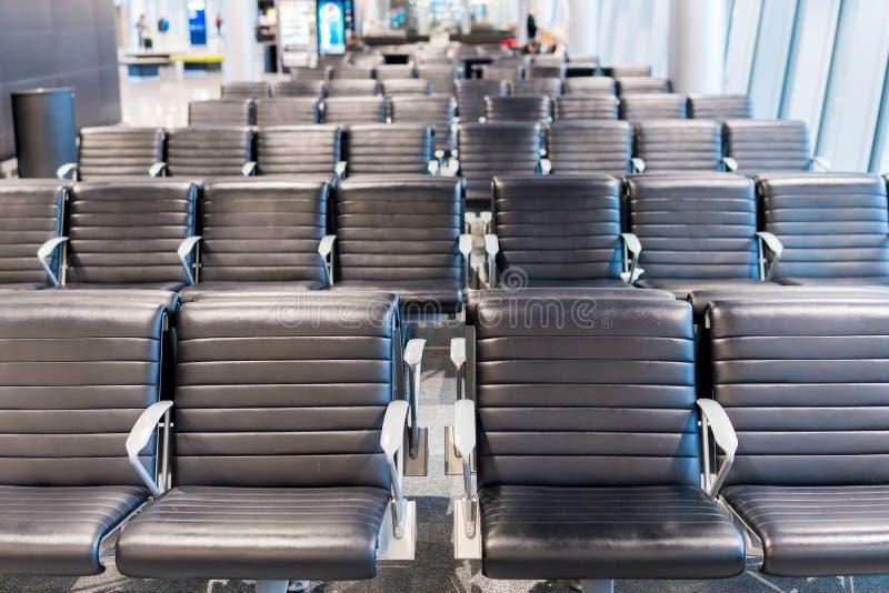 La zona de espera vacía del terminal de aeropuerto con las sillas gandulea con los asientos en el aeropuerto imagen de archivo
