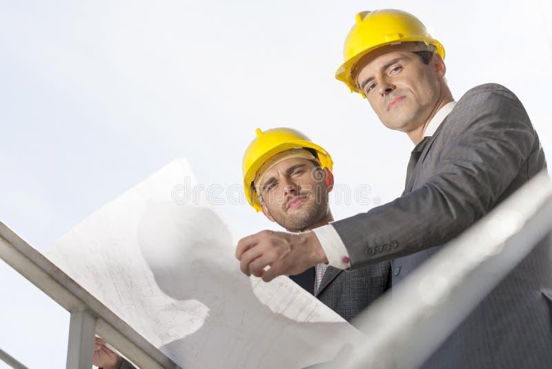 Laag hoekportret van zekere jonge zakenlieden die blauwdruk houden tegen duidelijke hemel stock foto