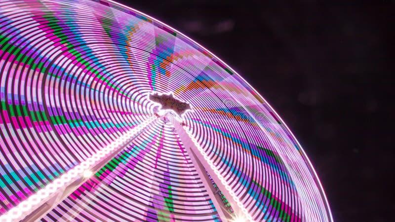 Laag hoekschot van een kleurrijke die pretparkrit bij nacht met een pikzwarte achtergrond wordt genomen stock afbeeldingen