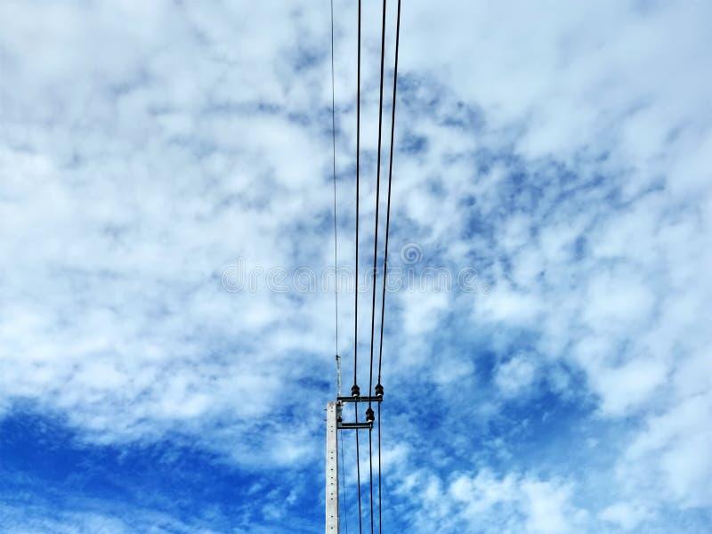 Laag Hoekweergeven van Elektropool en Kabels tegen Blauwe Bewolkte Stormachtige Hemel stock foto